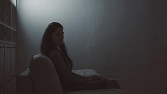 mulher deprimida em um quarto escuro