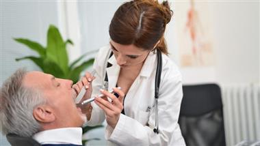 Doctor checks patient's tonsil