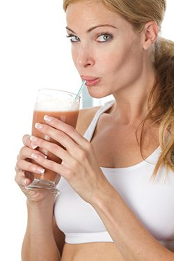 woman sipping protein drink