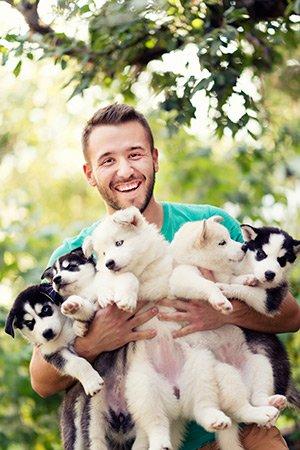 man holding puppies