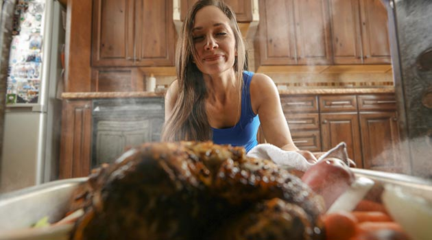 Woman pulling chicken out of oven