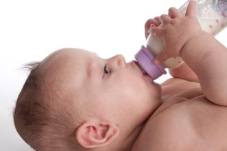 baby drinking artificial human milk