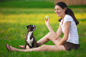 Woman playing ball with small breed dog