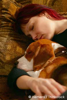 Woman sleeping with pet dog