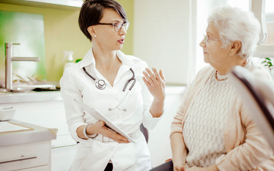의사와 이야기를 나누는 노인 여성
