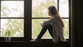 jeune fille triste qui regarde par la fenêtre