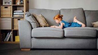 une fillette qui joue sur un canapé
