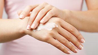 Une femme qui applique de la crème solaire sur sa main