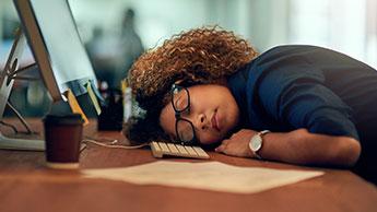 Mulher dormindo em sua mesa de escritório
