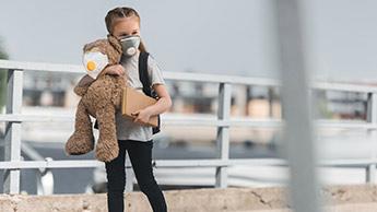 Kind, das eine Mundmaske gegen die Luftverschmutzung trägt
