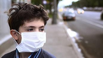 Kind trägt Maske gegen Luftverschmutzung