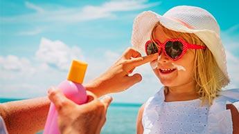 une mère applique de la crème solaire sur sa fille
