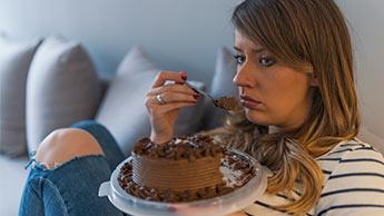 感情的にケーキを食べている女性