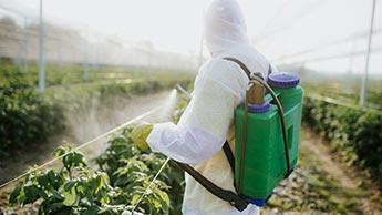 un agriculteur qui répand des pesticides