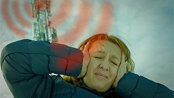 Frau in der Nähe eines Mobilfunkmasten leidet unter Schmerzen