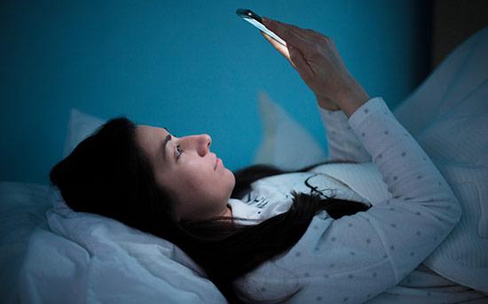 밤에 휴대폰을 보는 여자